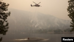 A helicopter gathers water from Blue Lake while fighting the Okanogan Complex fire in the Sinlahekin Wildlife Area near Loomis, Washington, Aug. 25, 2015.