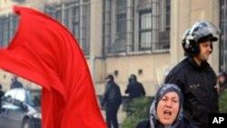 1月14日突尼斯抗议民众与安全部队发生冲突,一名妇女挥舞突尼斯国旗