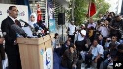 Le directeur de campagne d'Ennahda, Abdelhamid Jlazzi (à g.) devant son QG à Tunis (24 octobre 2011)
