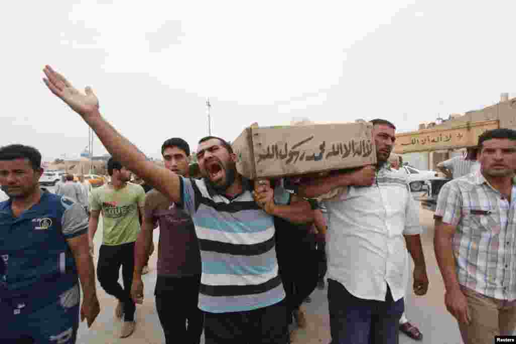 Relatives carry the coffin of an Iraqi police officer killed by militants, Najaf, Iraq, May 20, 2013.