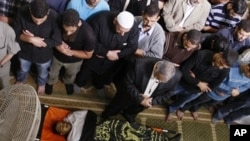 Palestinians pray over the bodies of four Islamic Jihad militants killed in Israeli airstrikes Saturday, during his funeral in Gaza City, Sunday, Oct. 30, 2011