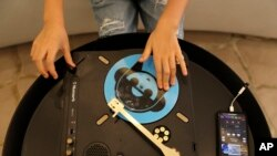 Michelle Rasul enjoys scratching her turntable in the lobby of her apartment building in Dubai, United Arab Emirates, Sunday, May 9, 2021. (AP Photo/Kamran Jebreili)