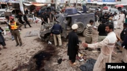 Petugas keamanan berusaha mengumpulkan bukti sesudah terjadi ledakan di Peshawar, 14/3/2014. Kelompok Pakistan Taliban yang berjuang untuk menjatuhkan pemerintahan Pakistan berada di ambang perpecahan.