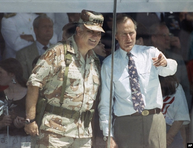 U.S. General Norman Schwarzkopf and then President George H. W. Bush watch the National Victory Parade from the viewing stand in Washington on June 8, 1991.
