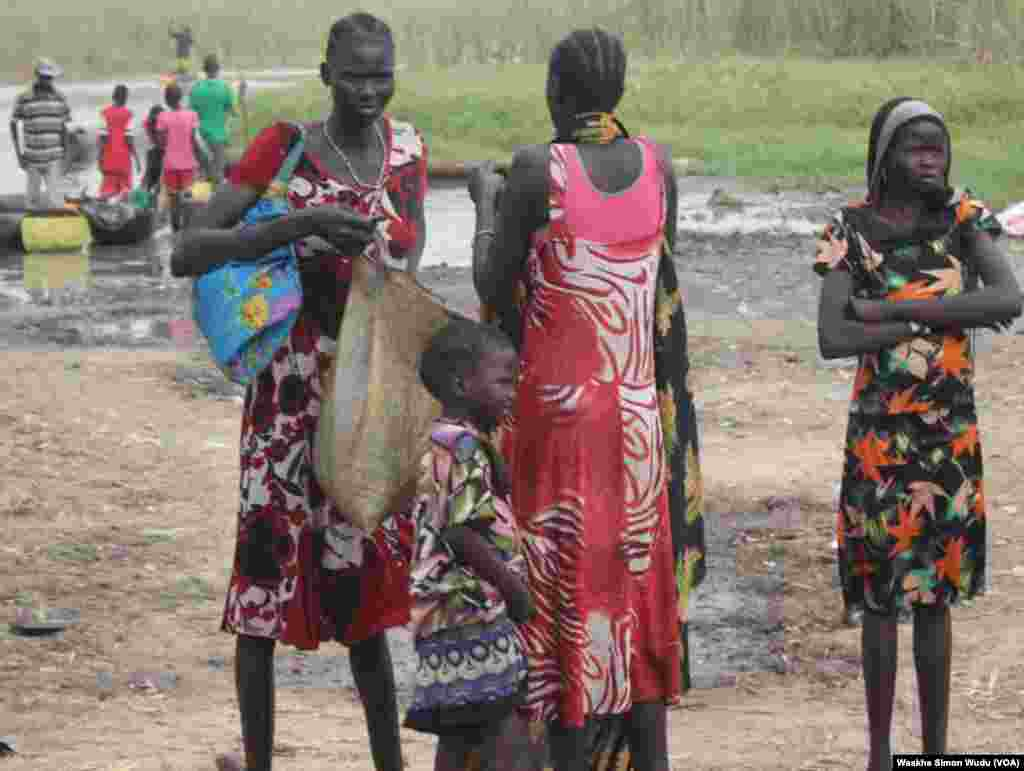 Women and girls stand on shore near the Sudd wetlands in southern Unity state in South Sudan on Saturday, March 21, 2015. Hundreds of South Sudanese are sheltering in the wetlands and come into the town of Ganyiel to pick up food provided by aid agencies.