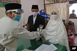 Bride Karlina and groom Cahya Sudrajat receive their marriage certificate from Muslim officiant Solehchudin while all wear protective gears to prevent the spread of the coronavirus during a wedding ceremony in Jakarta, Indonesia, Friday, June 19, 2020. (AP)
