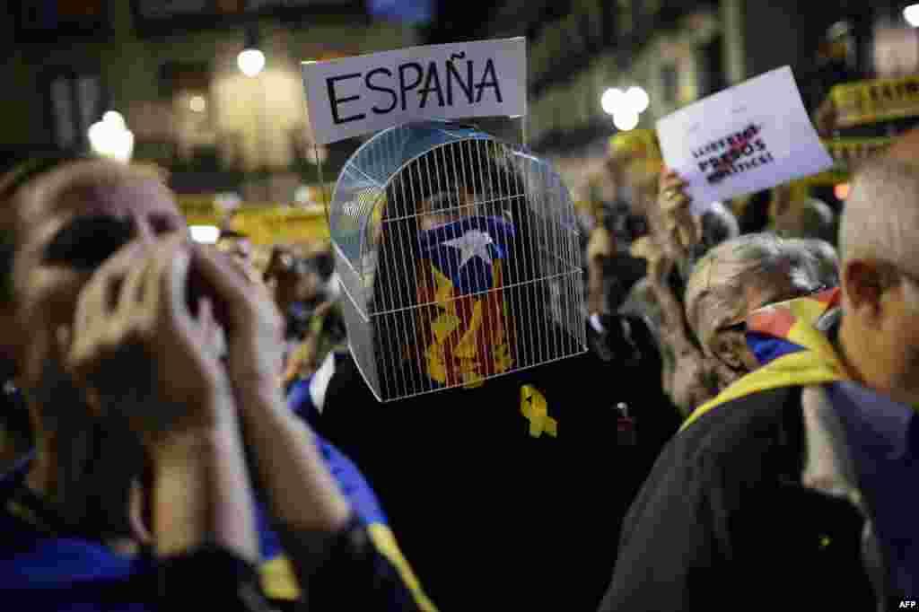 ស្ត្រីម្នាក់ដែលមានទូលទ្រុងនៅលើក្បាលរបស់នាង និងមានបិទមុខដោយទង់ជាតិEstelada ដែលទាមទារឯករាជ្យសម្រាប់តំបន់Catalonia ចូលរួមក្នុងបាតុកម្មនៅទីក្រុងBarcelona ដើម្បីប្រឆាំងនឹងការឃុំខ្លួនមន្ត្រី Catalan នៅក្នុងទីក្រុងម៉ាឌ្រីដ។