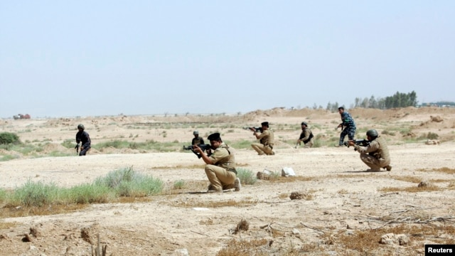 Members of Iraqi security forces take positions during a patrol looking for militants of the Islamic State of Iraq and the Levant (ISIL) west of Kerbala, June 29, 2014.