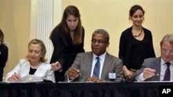 克林顿国务卿(左二)与海地总理贝勒里夫(中)和法国外长库什内(右)签署海地重建项目备忘录