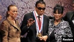 El exboxeador Mohamed Ali saluda luego de recibir la Medalla de la Libertad, el jueves por la noche en Filadelfia. Le acompañan su esposa Lonnie (izquierda) y su cuñada Marilyn Williams.