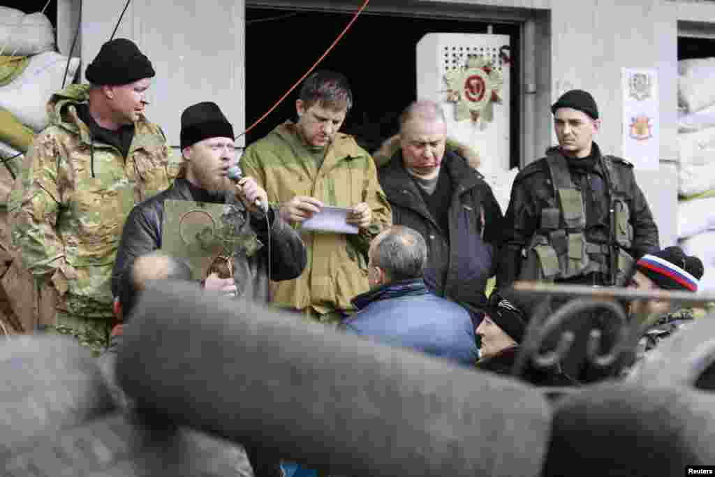 A clergyman addresses pro-Russian protesters during a rally in front of the seized office of the SBU state security service in Luhansk, eastern Ukraine, April 14, 2014.