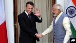 French President Emmanuel Macron waves to media as he shakes hand with Indian Prime Minister Narendra Modi before their meeting in New Delhi, India, March 10, 2018. Macron who is on a four-day state visit is expected to hold talks with Indian Prime Minist