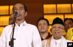 Capres 01 Joko Widodo (kiri) didampingi Cawapres Ma'ruf Amin berpidato dalam konferensi pers di Jakarta, Rabu 17/4 (AP Photo/Achmad Ibrahim).