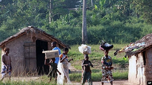 Ivorian refugees walk in the village of Loguatuo as many have flooded into Liberia, (File)