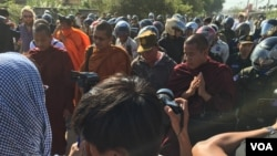 A group of Cambodian monks hold a Buddhist ceremony for protesters killed in early 2014, as police and security personnel are seen surrounding the monks, on Sunday, January 03, 2016. (Hul Reaksmey/VOA Khmer)