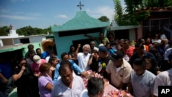 A family member laments the death of 64-year-old Reynalda Matus, as mourners prepare to bury her at the Miercoles Santo Cemetery in Juchitan, Oaxaca state, Mexico, Sept. 9, 2017. Matus was killed during a massive earthquake.