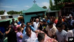 A family member laments the death of 64-year-old Reynalda Matus, as mourners prepare to bury her at the Miercoles Santo Cemetery in Juchitan, Oaxaca state, Mexico, Sept. 9, 2017. Matus was killed when the pharmacy where she worked nights collapsed during Thursday's massive earthquake.