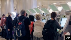 FILE - Passengers arriving from abroad at Los Angeles International Airport use new automated passport kiosks.
