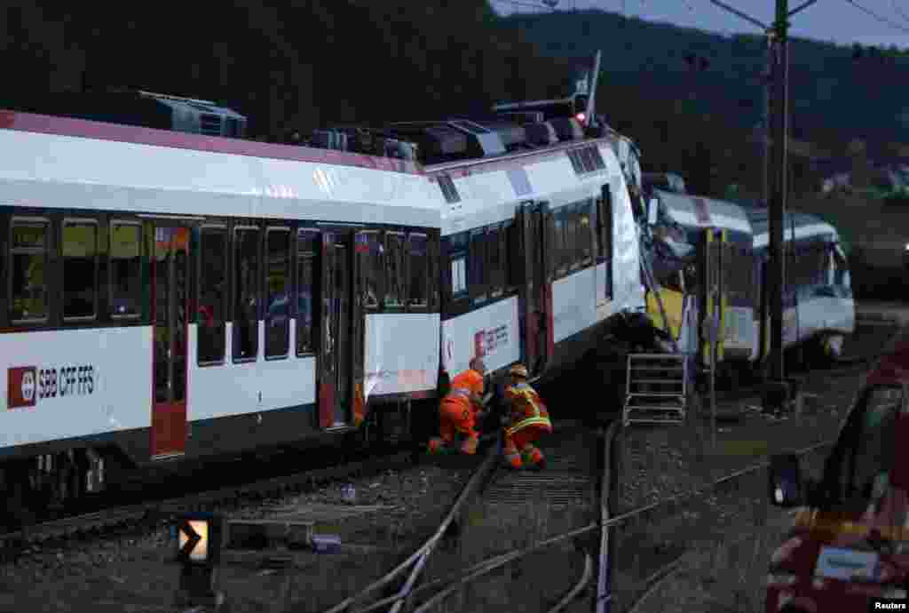 Rescue workers at the site of a head-on collision between two trains near Granges-pres-Marnand, Switzerland, July 29, 2013.