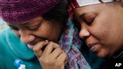 미국 뉴욕 건물 붕괴 사고로 집을 잃은 주민(왼쪽)이 12일 지인의 위로를 받고 있다.