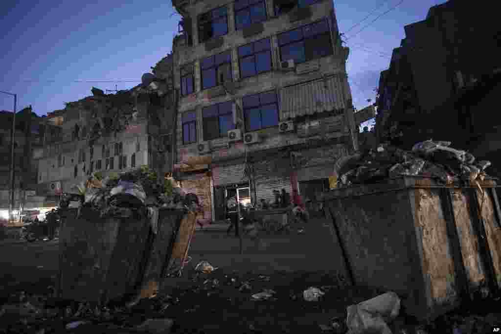 Hələbdə sakinlər Azad Suriya Ordusu ilə hökumət qüvvələrinin toqquşmaları nəticəsində dağılmış binaların yaxınlığında bazarlıq edirlər. Hələb, Suriya, 9 dekabr 2012.