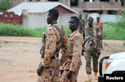 FILE - South Sudanese policemen and soldiers stand guard along a street following renewed fighting in South Sudan's capital Juba, July 10, 2016.