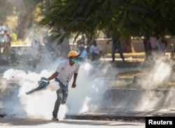 A demonstrator picks up a tear gas canister during protests against Haiti's President Jovenel Moise, in Port-au-Prince, Haiti, Feb. 8, 2021.