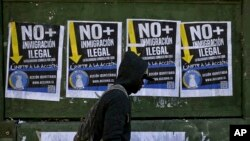 """A migrant walks past anti-migrant posters that read in Spanish """"No more illegal immigration. Solidarity begins at home"""" prior to a march in favor of migrants, organized by the National Immigrants Coordinator, in Santiago, Chile, Aug. 20, 2017."""