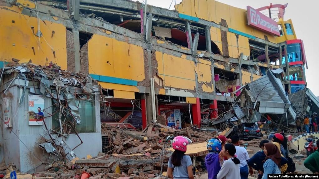 Người dân đứng trước một trung tâm mua sắm đổ sập sau khi một trận động đất làm rung chuyển thành phố Palu, đảo Sulawesi, Indonesia, ngày 29 tháng 9, 2018.