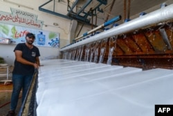 Seorang pekerja tengah mengamati proses pembuatan balok es di sebuah pabrik di kota Mosul, 3 Juli 2021, di tengah pemadaman listrik dan suhu udara panas yang melanda kota tersebut. (AFP)
