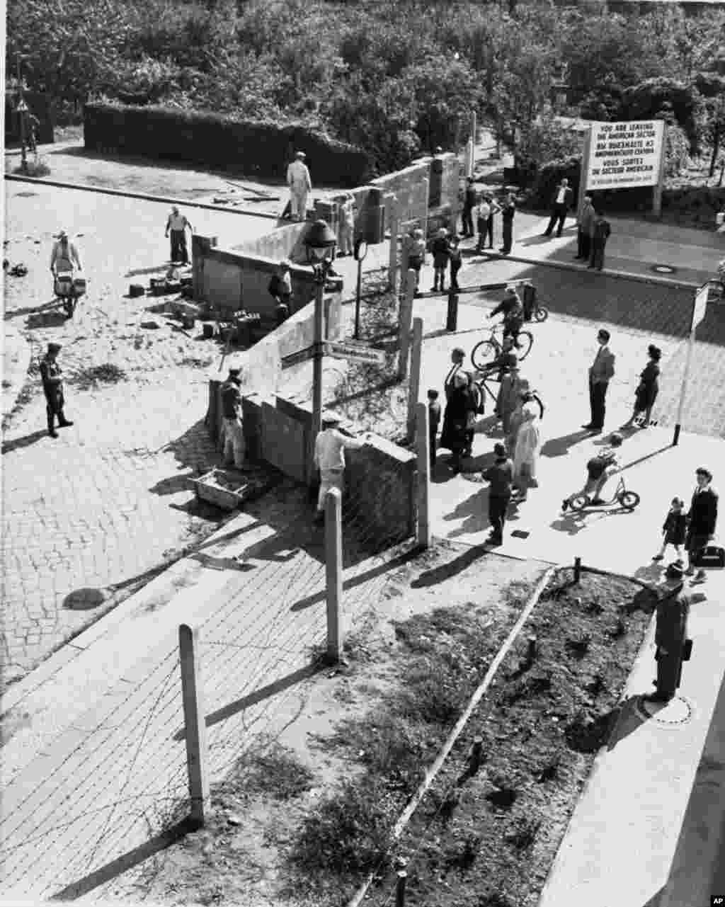 ARCHIV - Westberliner schauen im August 1961 Ostberliner Arbeitern bei der Errichtung der Berliner Mauer an der Wildenbruchstrasse und Heidelbergerstrasse zu. Am Donnerstag, den 13. August 2009, jaehrt sich der offizielle Tag des Mauerbaus zum 48. Mal. (