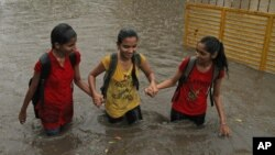 FILE - Indian girls hold hands and wade through a waterlogged street .