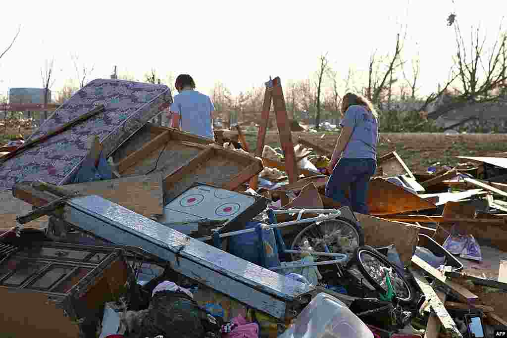 People walk through debris caused by a tornado that blasted Harrisburg, Illinois, February 29, 2012. (AP)