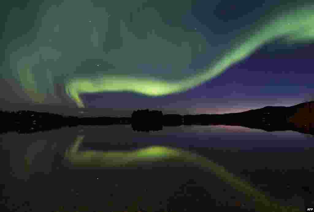 'Aurora Borealis' atau pancaran cahaya berkilauan pada lapisan ionosfermenghiasi langit di desa Erikslund, Vaesternorrland, Swedia.