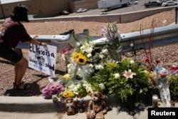 Seorang prempuan meletakkan plakat untuk menghormati para korban penembakan massal di Walmart, El Paso, Texas, AS 4 Agustus 2019.