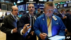 Traders Andrew Silverman, Gregory Rowe, and James Lamb, left to right, work on the floor of the New York Stock Exchange, Aug. 15, 2019.