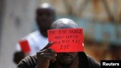Waandamanaji waonyesha kadi nyekundu kuashiria kumalizika kwa utawala wa Rais Kabila mjini Kinshasa Jumatatu.