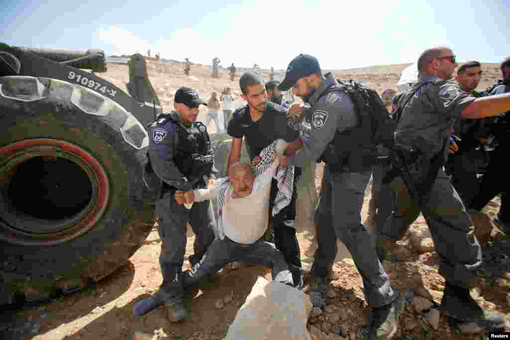 Israeli policemen detain a Palestinian protesting Israel's plan to demolish the Palestinian Bedouin village of Khan al-Ahmar, in the occupied West Bank.