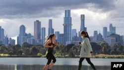 People exercise in front the city skyline in Melbourne on August 29, 2021, as authorites announced the extension of an ongoing coronavirus lockdown in Australia's second-biggest city. (Photo by William WEST / AFP)