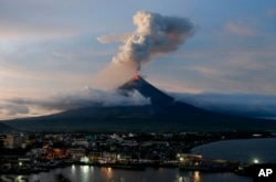 With Legazpi city in foreground, the Mayon volcano erupts anew at dusk, Jan. 25, 2018, in Albay province about 200 miles (340 kilometers) southeast of Manila, Philippines.