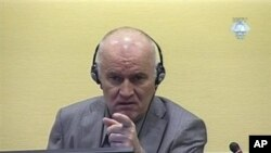 In this image made from television, former Bosnian Serb Gen. Ratko Mladic gestures during his initial appearance at the U.N.'s Yugoslav war crimes tribunal in The Hague, Netherlands, June 3, 2011