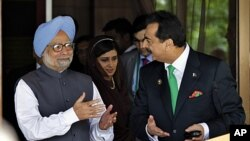 Pakistani Prime Minister Yousuf Raza Gilani, right, and Indian Prime Minister Manmohan Singh gesture after their meeting on the sidelines of the South Asian Association for Regional Cooperation (SAARC) summit in Addu, Maldives, November 10, 2011.