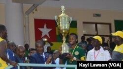 Le Premier ministre togolais Komi Sélom Klassou remet le trophée de la 7ème édition du tournoi de l'intégration de l 'UEMOA au capitaine du Sénégal, Togo, 3 décembre 2016. VOA/Kayi Lawson.