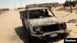 Sebuah mobil hancur terbakar pasca serangan militan di wilayah Sheikh Zuweid, dekat kota El-Arish di Jazirah Sinai, Mesir (10/9). Sedikitnya tiga orang tentara dilaporkan tewas dalam serangan militan di markas besar intelijen militer di kota Rafah (11/9).
