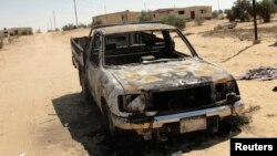 The wreckage of a burnt car is seen after assaults on militant targets by the Egyptian Army, in a village on the outskirts of Sheikh Zuweid, near the city of El-Arish in Egypt's Sinai peninsula, Sept. 10, 2013.