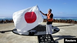日本东京都知事石原慎太郎在冲之鸟展示日本国旗(2005年5月20日)