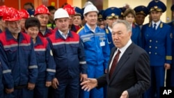 "Kazakhstan's president and the main presidential candidate, Nursultan Nazarbayev, answers questions while speaking to workers during the opening of the ""Moscow"" subway station of the Almaty metro system in Almaty, Kazakhstan, April 18, 2015."