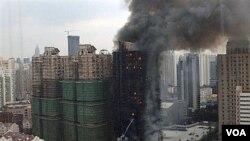 Asap mengepul dari sebuah gedung apartemen di kota Shanghai yang terbakar. Selain korban tewas, lebih dari 70 lainnya luka-luka.