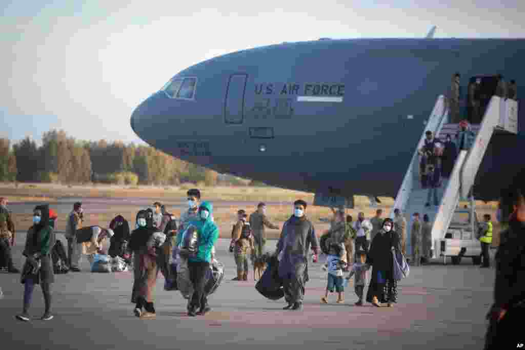 Evacuees from Afghanistan disembark from a U.S. Air Force plane at the Naval Station in Rota, Spain. The United States completed its withdrawal from Afghanistan, ending America's longest war.