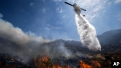 A helicopter drops water over a wildfire in Cabazon, California, August 8, 2013. About 1,500 people have fled and three are injured as a wildfire in the Southern California mountains quickly spreads.